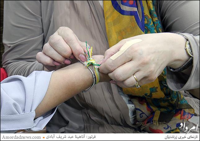 بستن دستبند تیروباد در جشن تیرگان بر دست یکدیگر