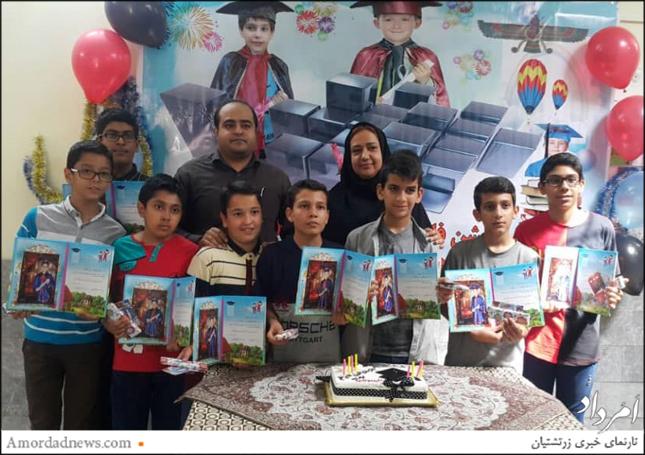 دانشآموزان با فریبا غیبی، آموزگار پایه ی ششم، و رامتین سلامتی، مدیر دبستان عکس یادگاری گرفتند