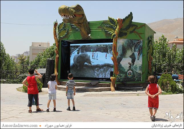 اسکرین بزرگ تلویزیونی که همراه تصاویر حیوانات ودایناسورها با تصویر افراد مقابل دوربین به نمایش در میآید