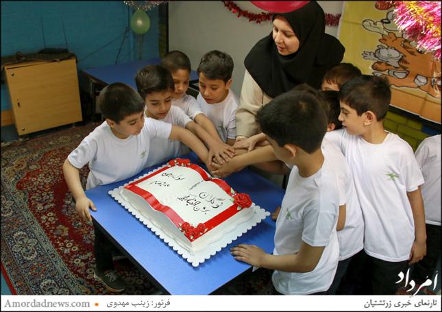 دانشآموزان به همراه آمنه مهماننواز، آموزگار پایهی یکم کیک حروف الفبا را بریدند